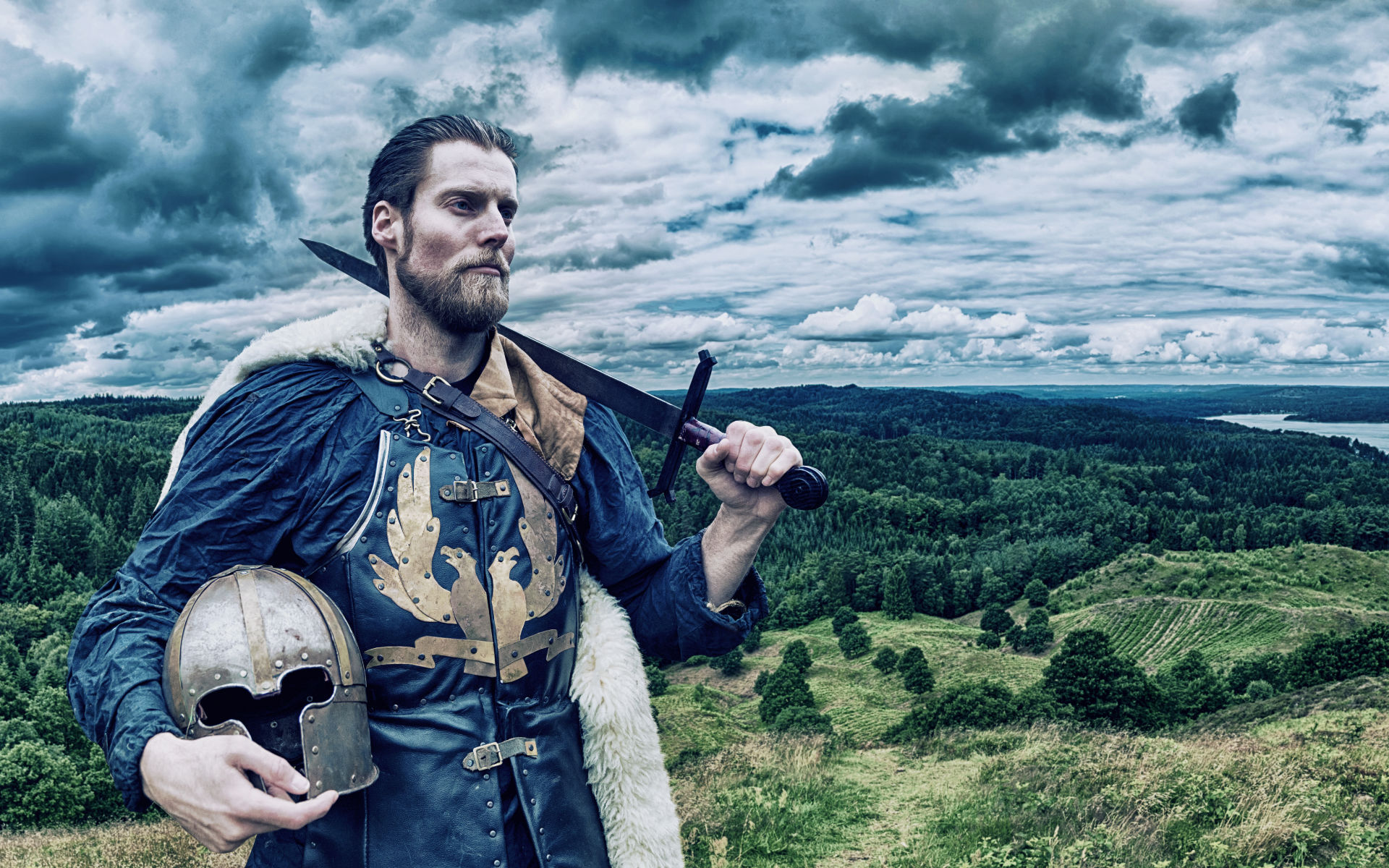 Viking warrior stands on hill overlooking the landscape